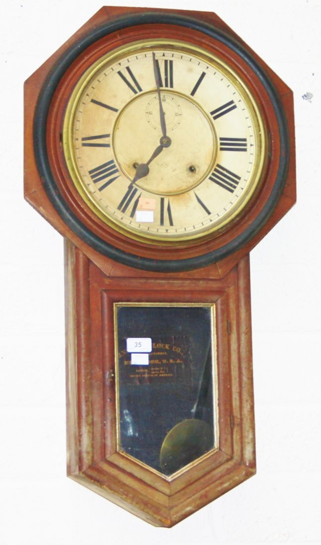 AN AMERICAN GRAINED WALNUT AND EBONISED WALL CLOCK,  by