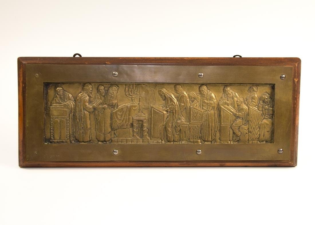 A CHASED PLAQUE OF JEWS PRAYING IN SYNAGOGUE.