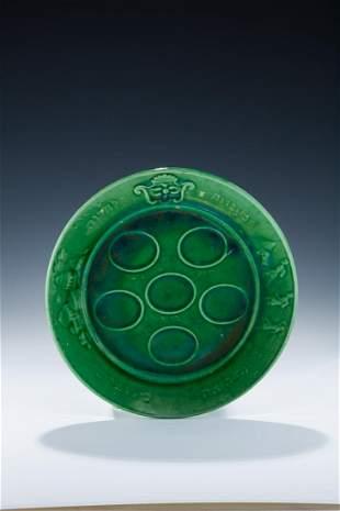A GREEN GLAZED SEDER PLATE