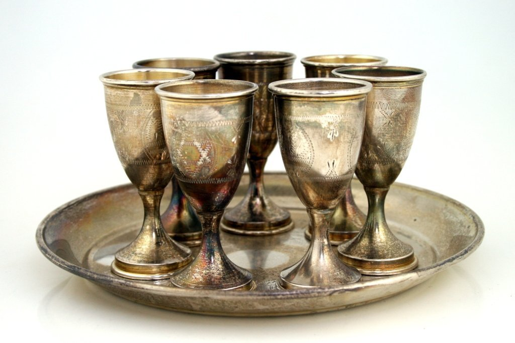 A SET OF SEVEN STERLING SILVER KIDDUSH CUPS AND UNDERPL