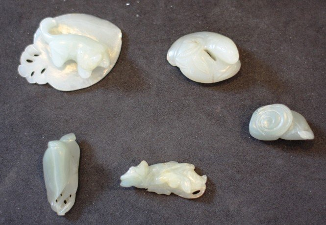 18: A collection of five celadon jade pendants