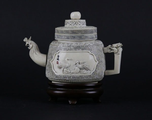 Well Carved Chinese Tea Pot on Wooden Stand. Dipicts