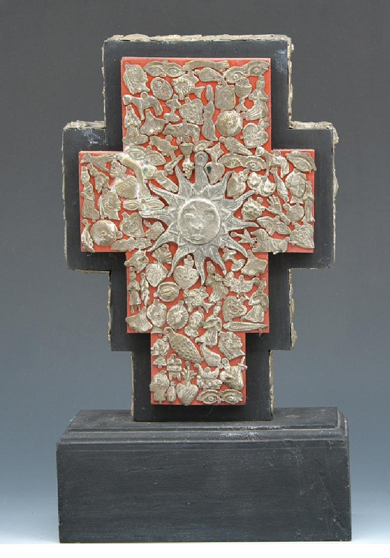 Mexican cross with milagros on stand