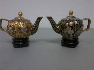 Pair of Chinese cloisonne teapots on the wooden s