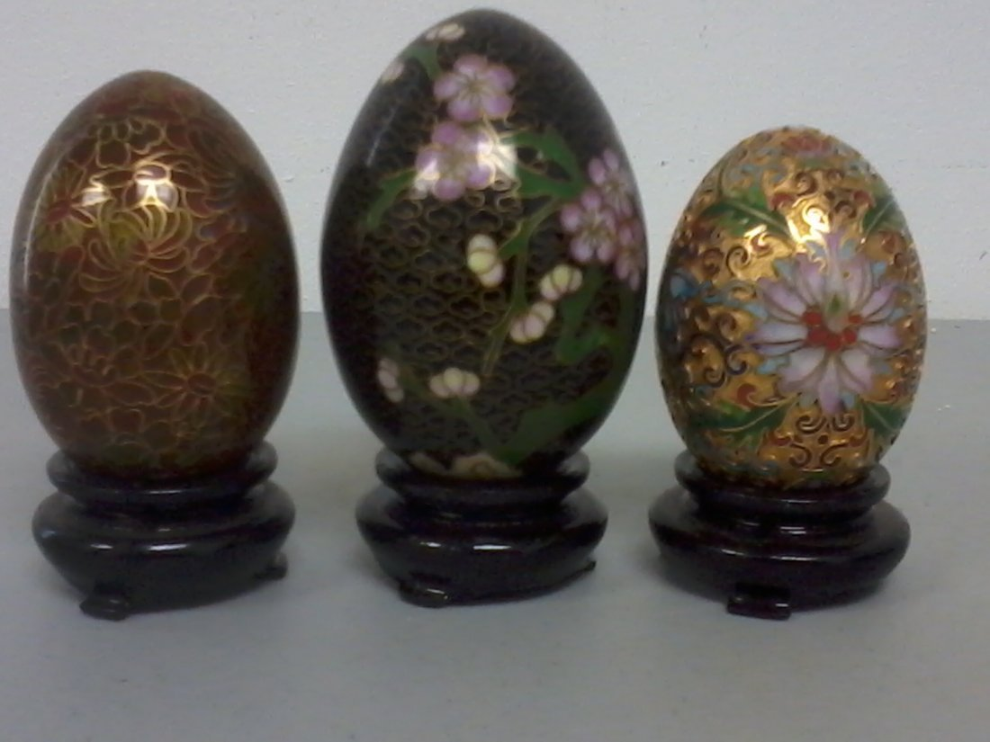 Set of three Chinese cloisonne eggs with wooden stands