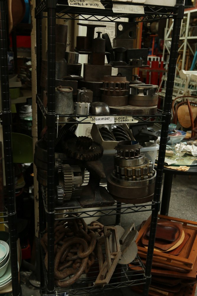 Three shelves of vintage metal blocks, gears, and