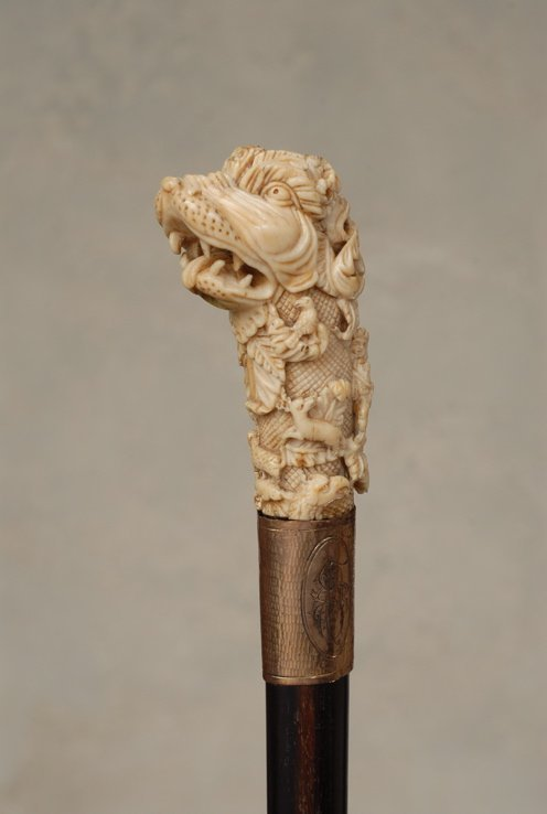 35: A great ivory cane of a stylized dog with hunters