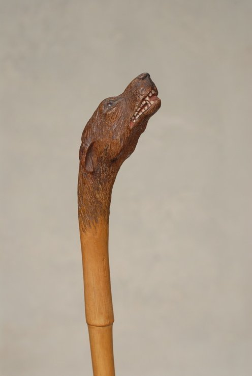 82: A carved wood cane of a howling dog