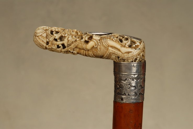 A Burmese ivory and silver cane of man in a demon mask