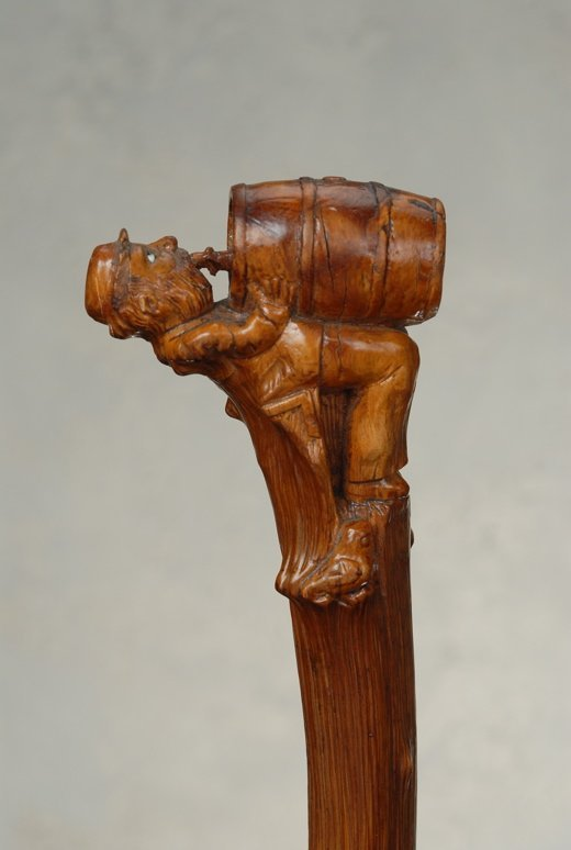 A carved wood cane of a man drinking from a keg