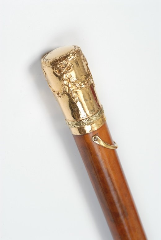 An English gold  cane with a wood storage tube