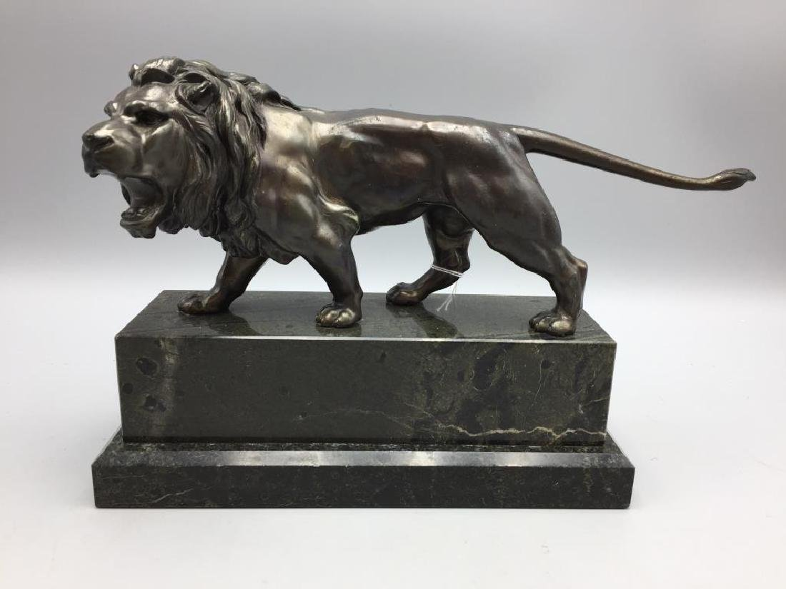 Metal statue of lion on marble base