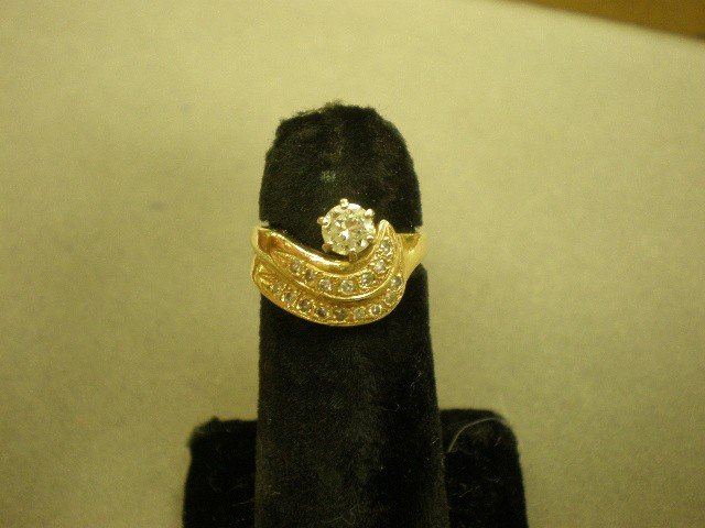 119: Diamond ring. 14K yg (marked) with swirl motif, co