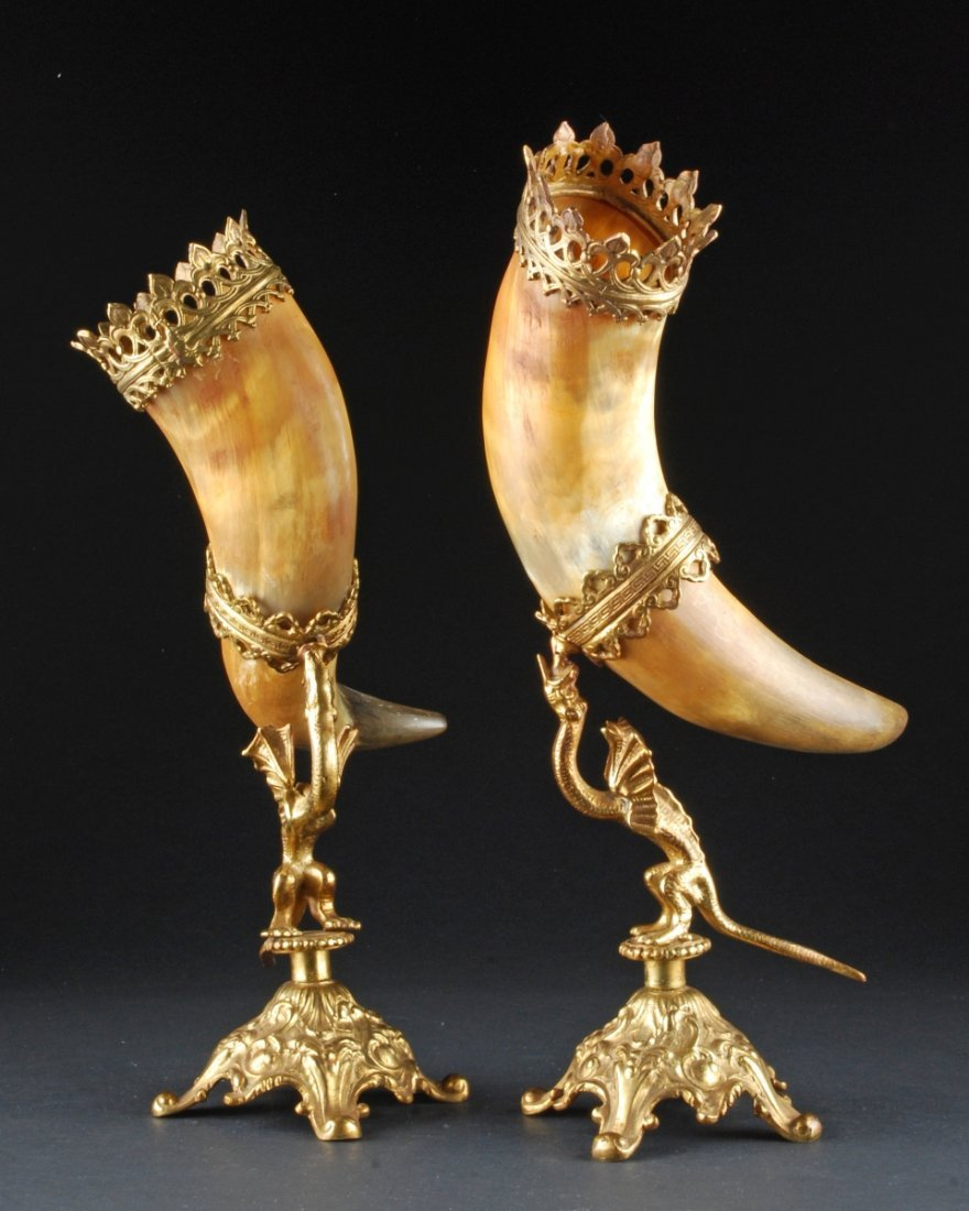 PAIR OF HORNS ON ORNATE MOUNTS, the horn supported by a