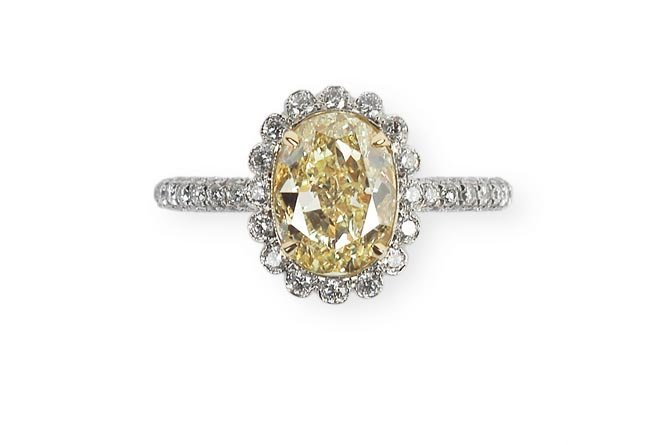 A Fancy Yellow Diamond and Diamond Ring Centered by an