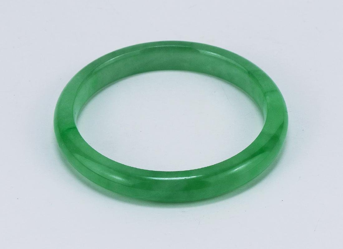 A GREEN JADEITE CARVED BANGLE