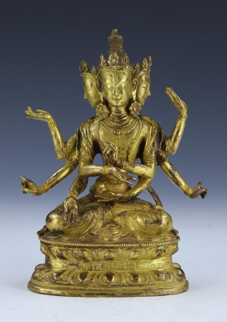 A CHINESE GILT BRONZE FIGURE OF GUANYIN WITH THREE FACE