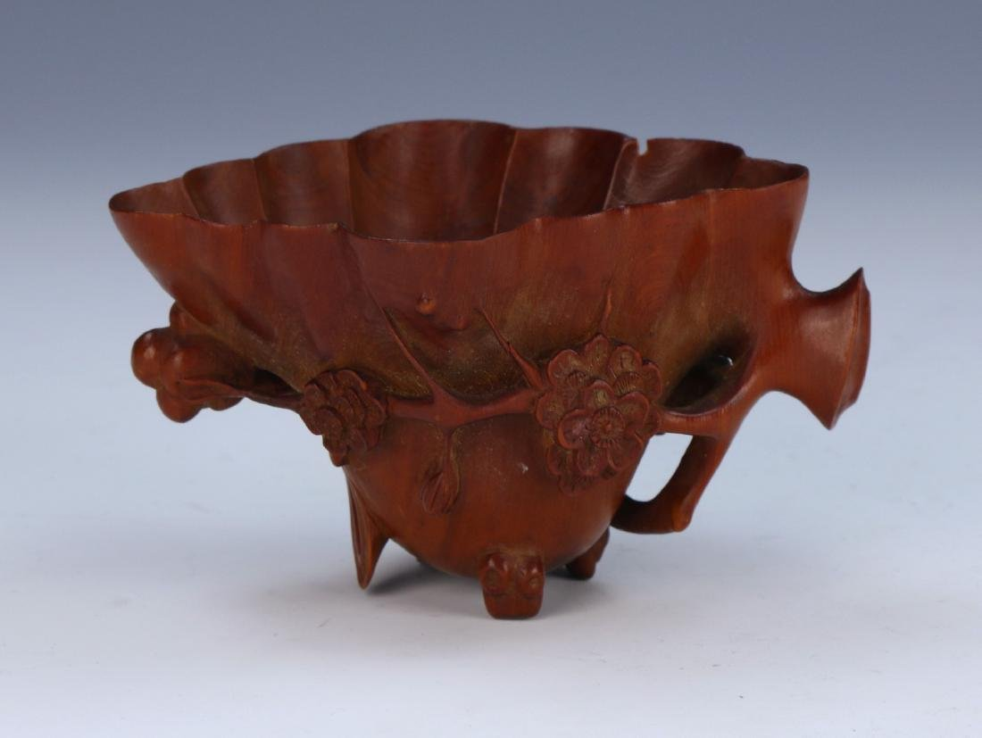 A CHINESE WOOD CARVED LIBATION CUP