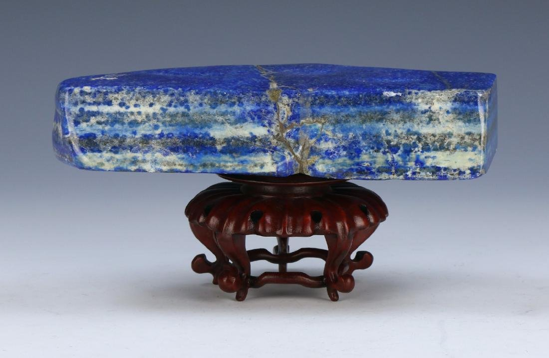 A LAPIS BLUE ROCK & WOODEN STAND
