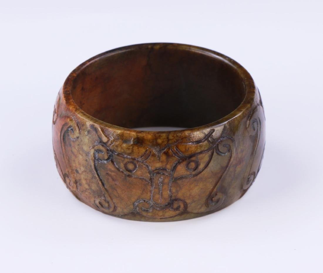 AN ARCHAIC JADE CARVED BANGLE