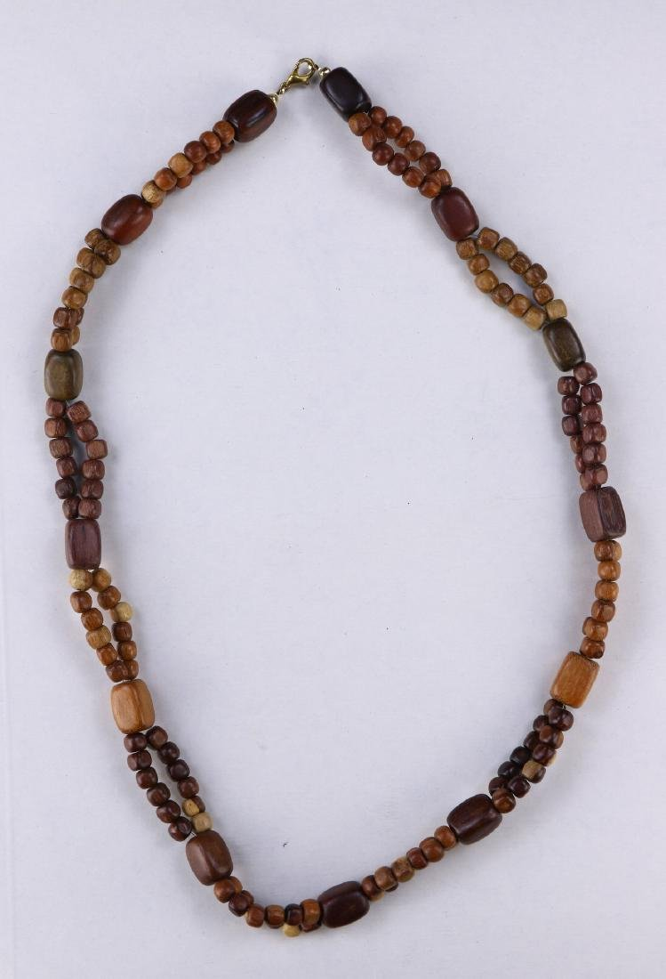 A CHINESE TAN WOOD CARVED NECKLACE