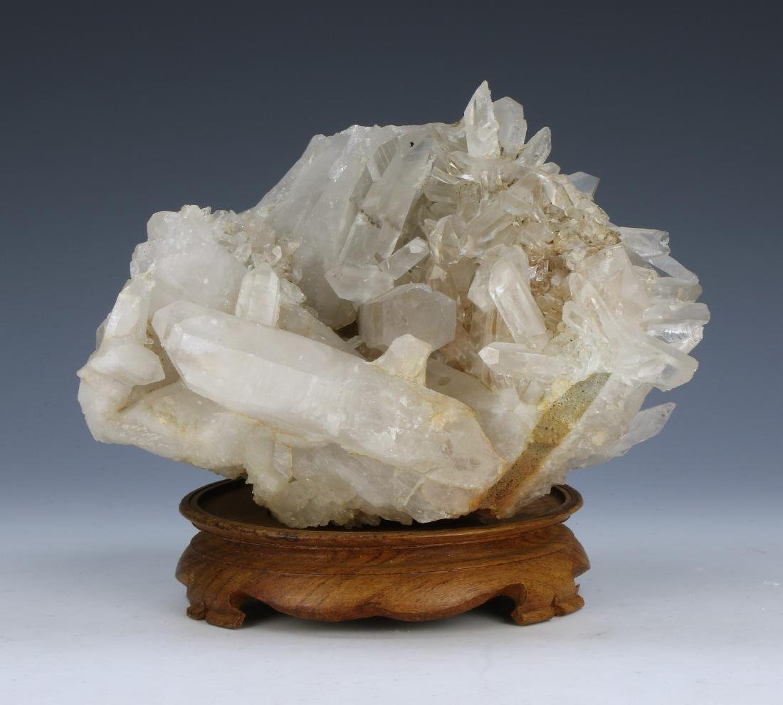 A CRYSTAL ROCK ON WOOD STAND