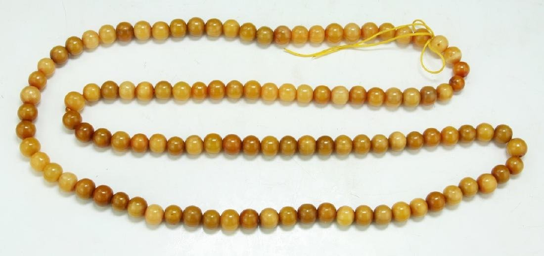 AN AMBER MILA BEAD NECKLACE