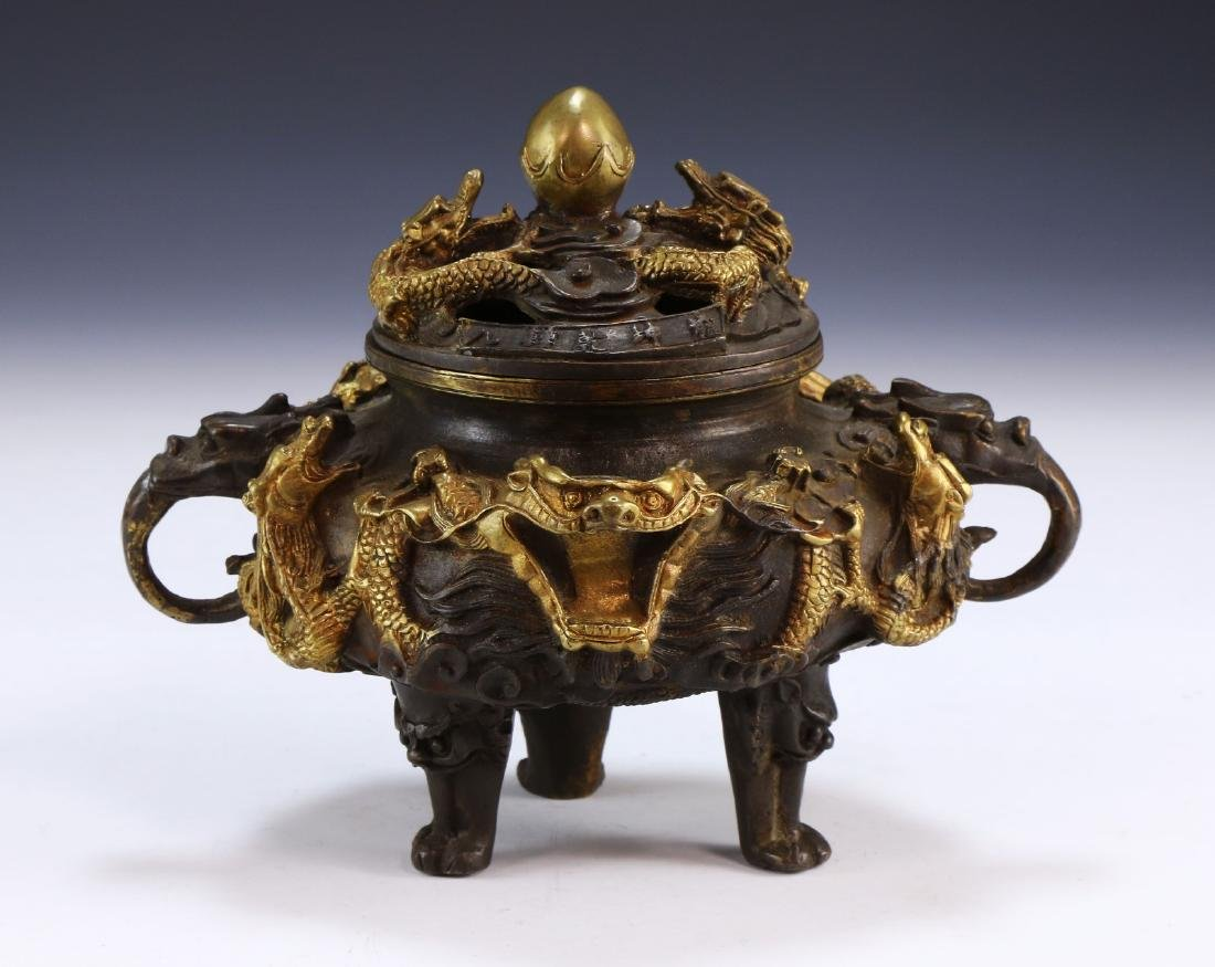 A CHINESE GILT BRONZE LIDDED TRIPOD CENSER