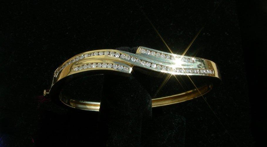 63: LADIES 14K YELLOW GOLD AND DIAMOND BANGLE BRACELET