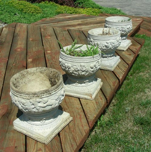 SET OF FOUR HEAVY CEMENT PLANTERS ON STANDS