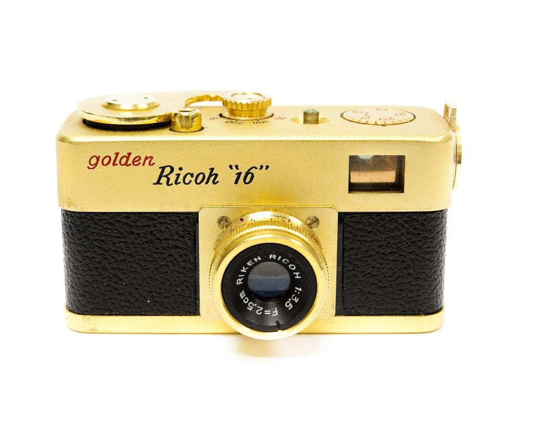 """Golden Ricoh """"16"""" Camera with Case."""