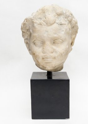 Ancient carved limestone head of a boy.