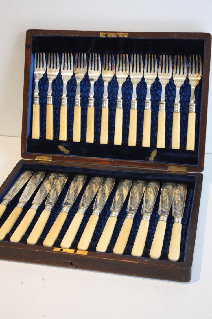 33: Ensemble de douze fourchettes et douze couteaux à p