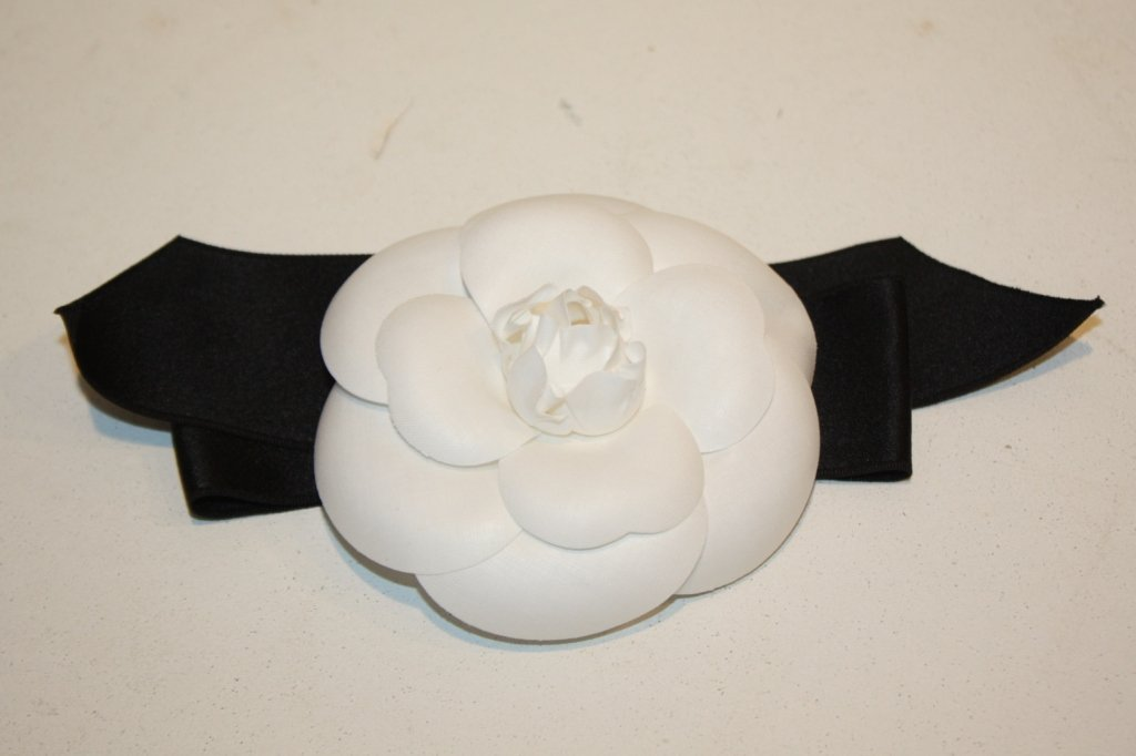 """1: CHANEL - Broche """"Camélia"""" blanc sur ruban noir, dans"""