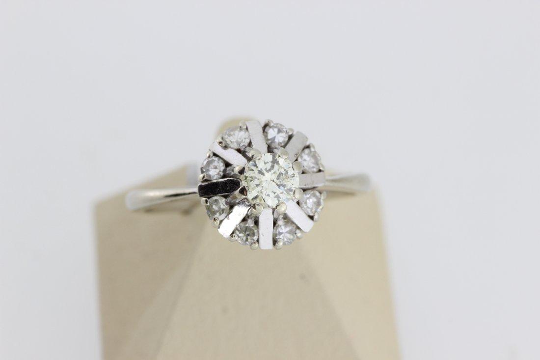 Bague en or ornée d'un diamant entouré de diamants. P 4