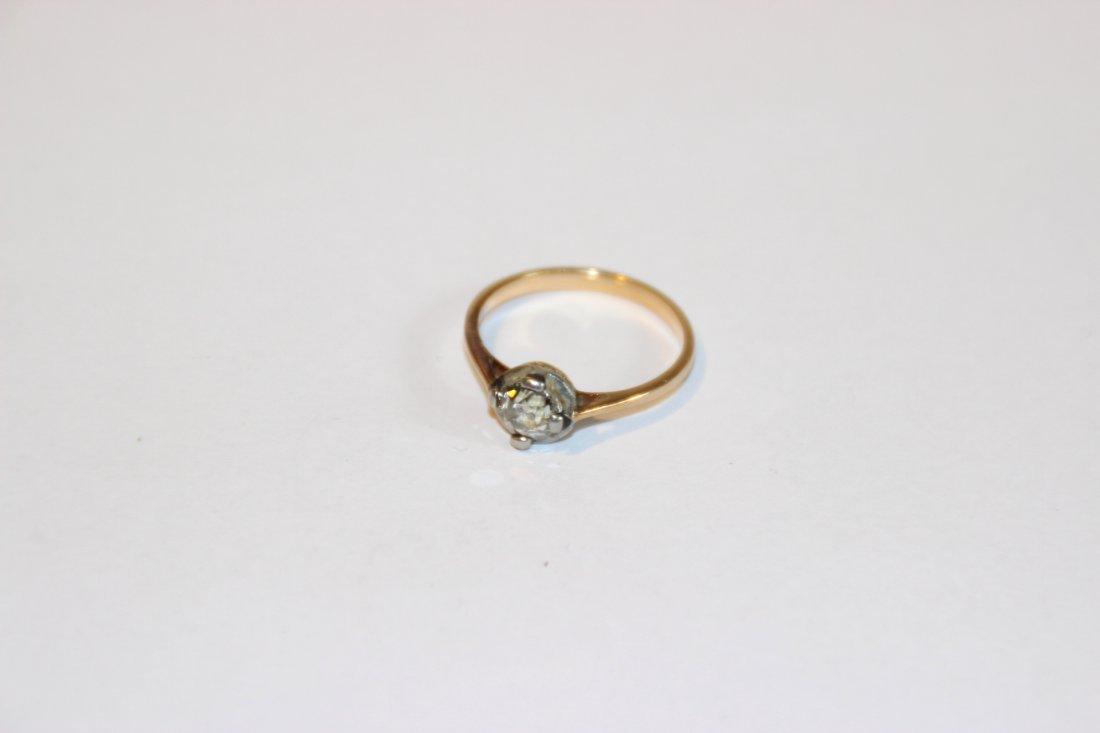 Bague solitaire en or jaune et blanc avec diamant.