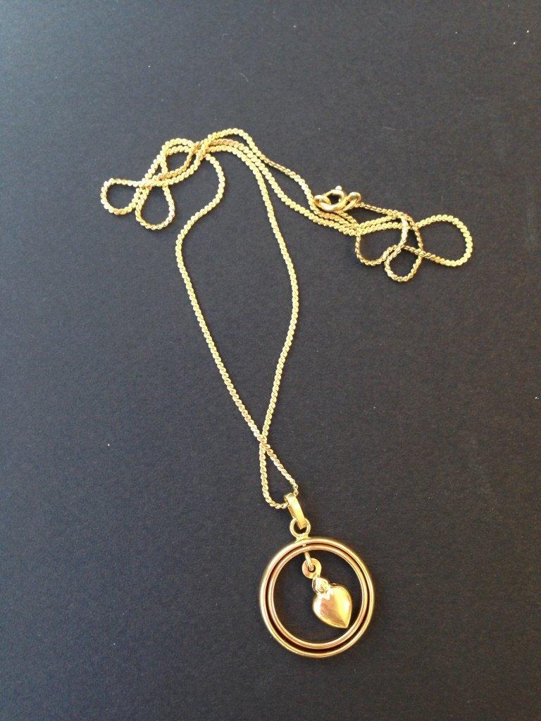 Collier en or jaune orné d'un pendentif cœur dans deux