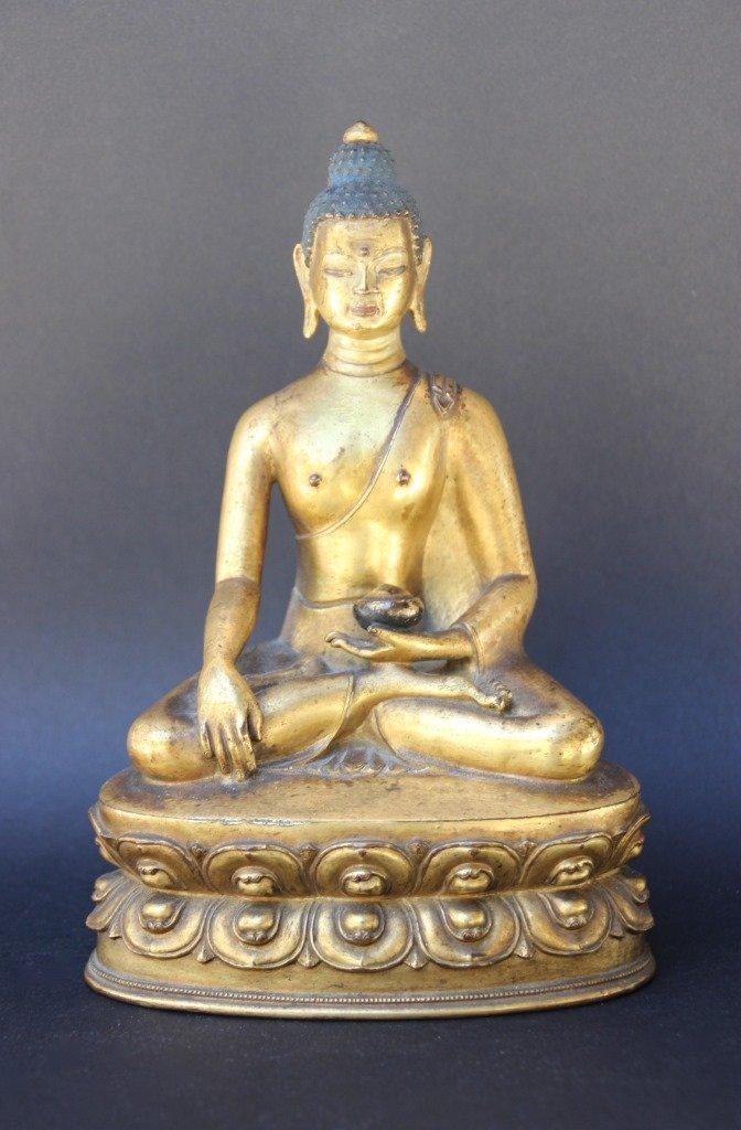 TIBET - XIXème  Buddha assis en bronze doré  Parchemins