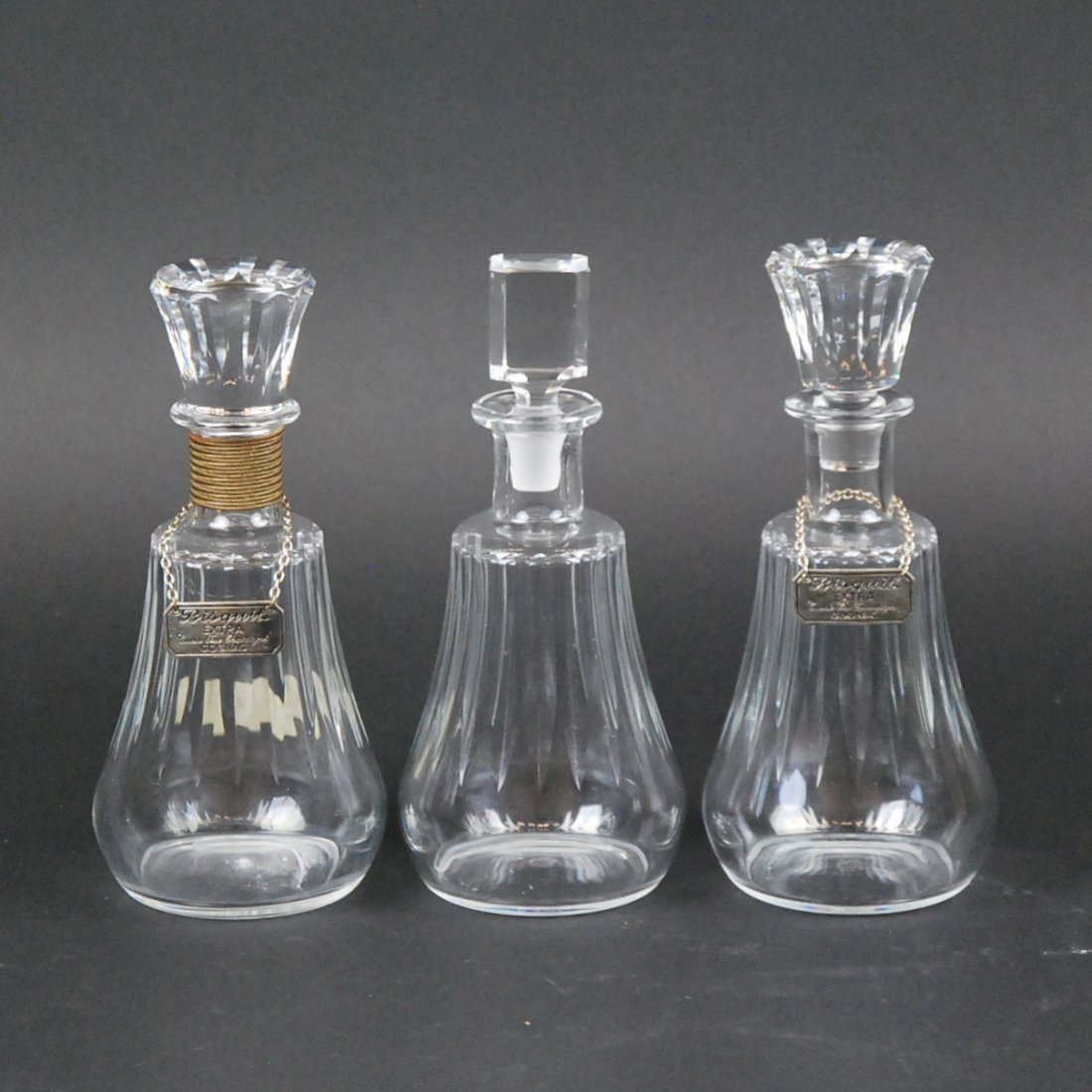 THREE BACCARAT GLASS DECANTERS WITH STOPPERS