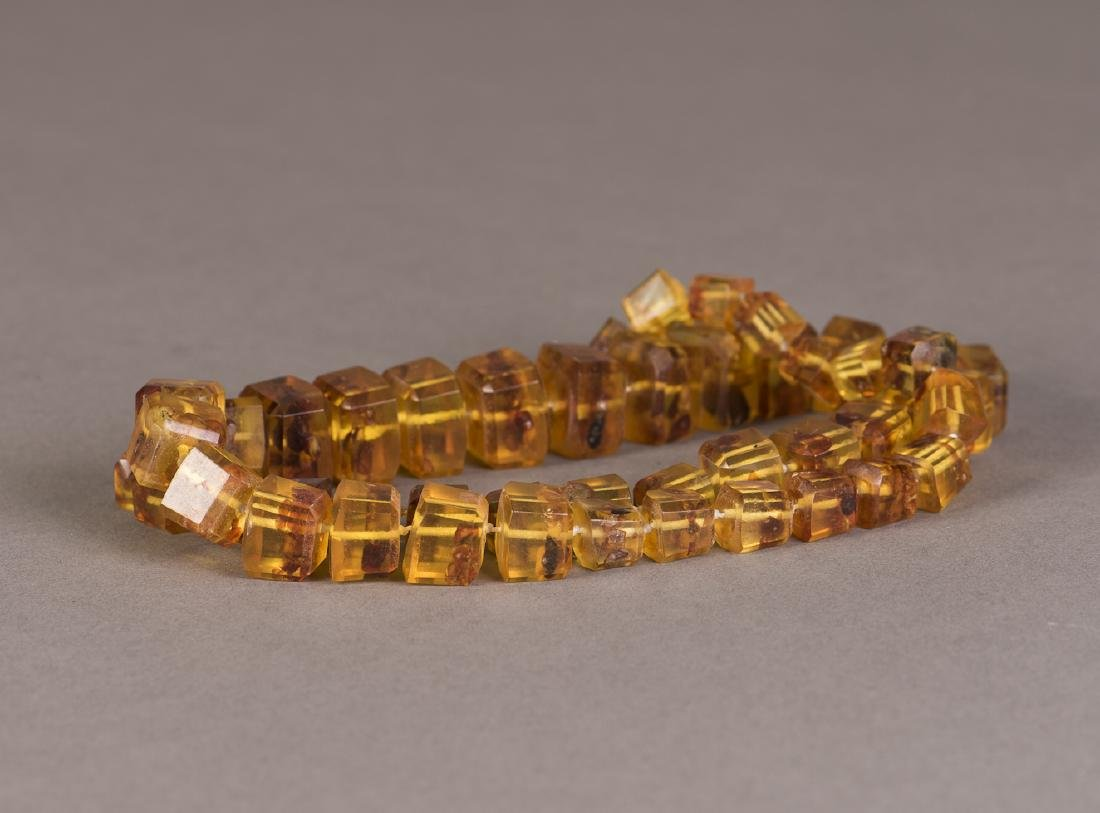 A STRAND OF CUBICAL BEADED BEESWAX NECKLACE