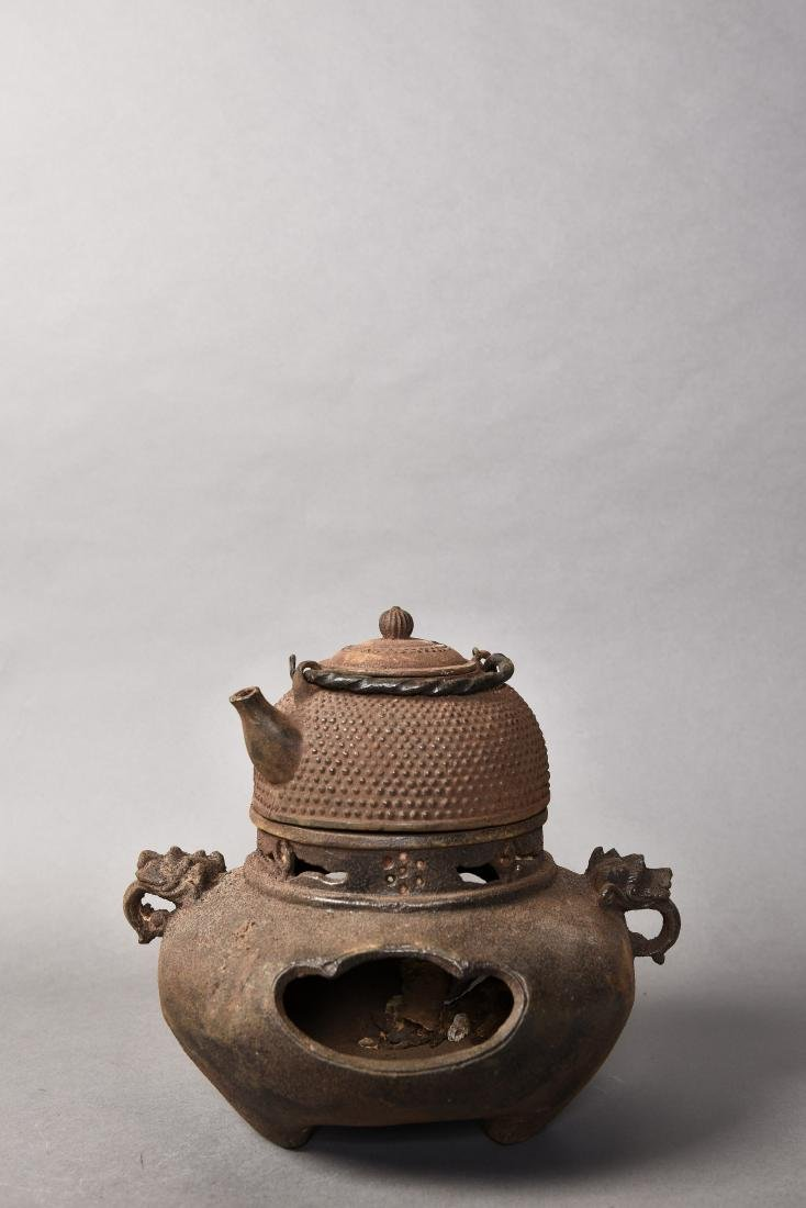 A IRON TEAPOT WITH A STOVE