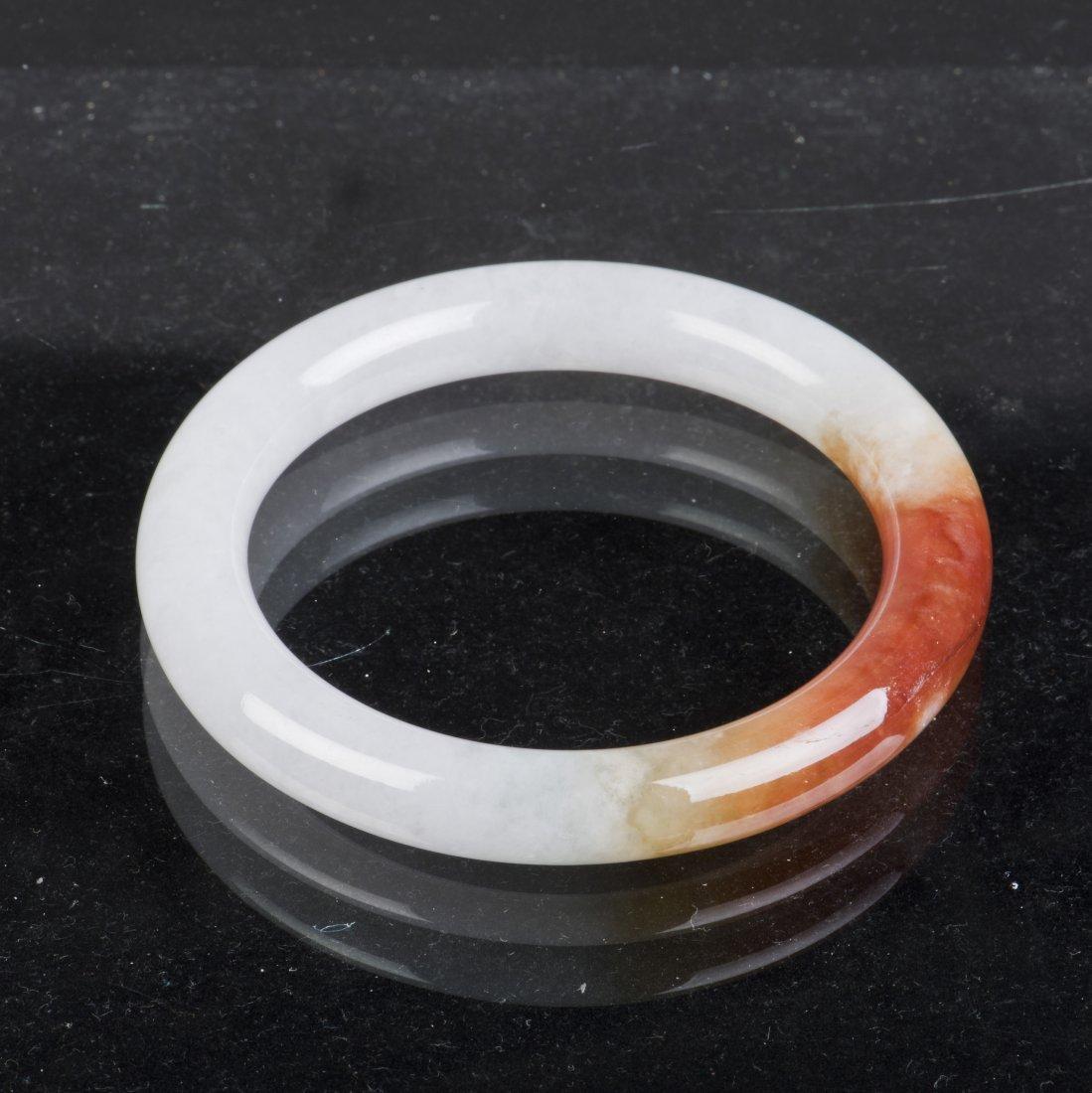 A JADE BANGLE OF VARIEGATED WHITE AND BROWNISH ORANGE,