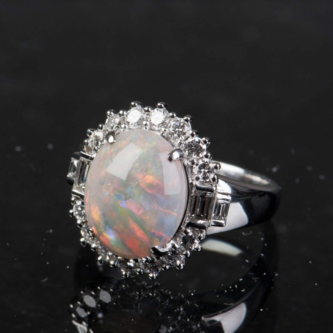 AN OVAL-CUT OPAL AND DIAMOND RING