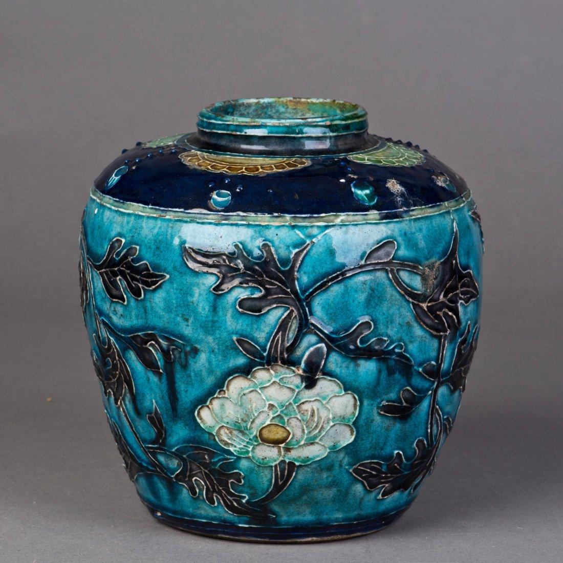 A COBALT GLAZED PORCELAIN JAR WITH FLOWER IN RELIEF