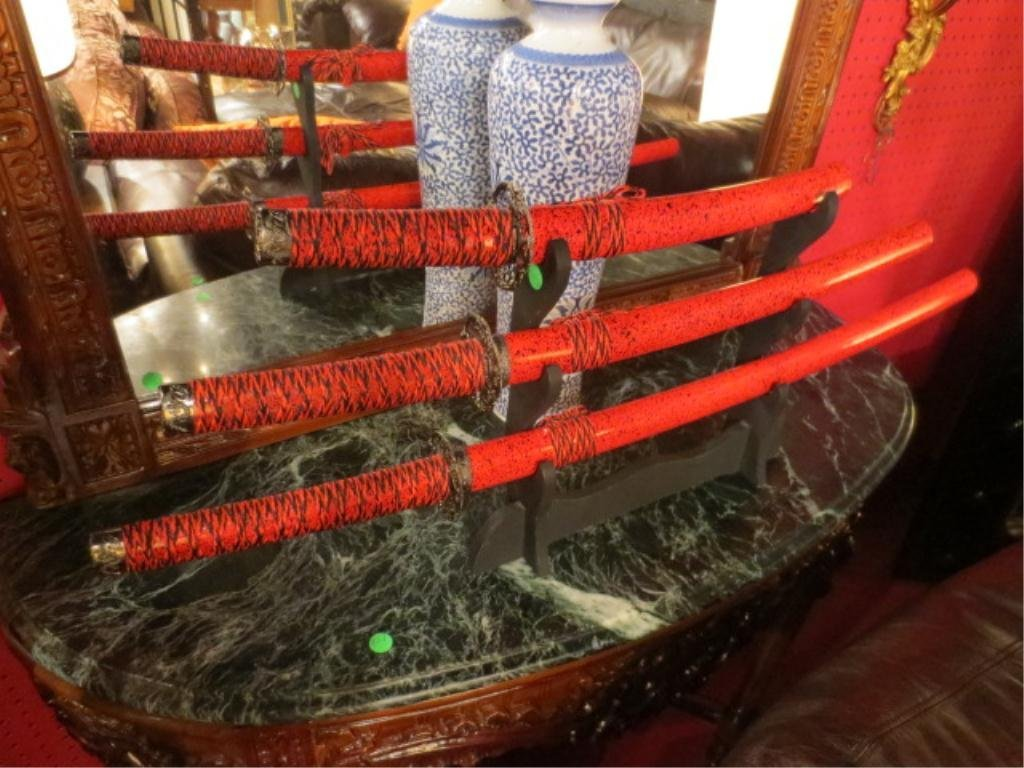 22: THREE DECORATIVE CHINESE SWORDS ON DISPLAY STAND, A