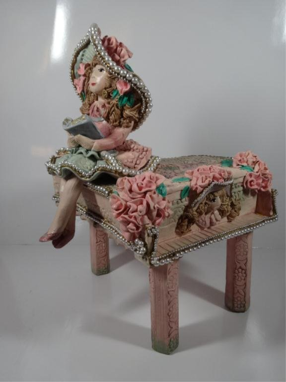 ART POTTERY GIRL SEATED ON PINK BABY GRAND PIANO,