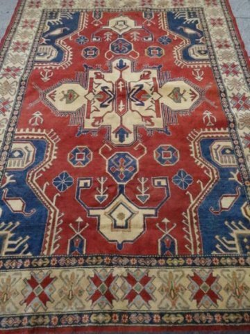 LARGE MIDDLE EASTERN WOOL RUG, RED FIELD WITH BLUE AND