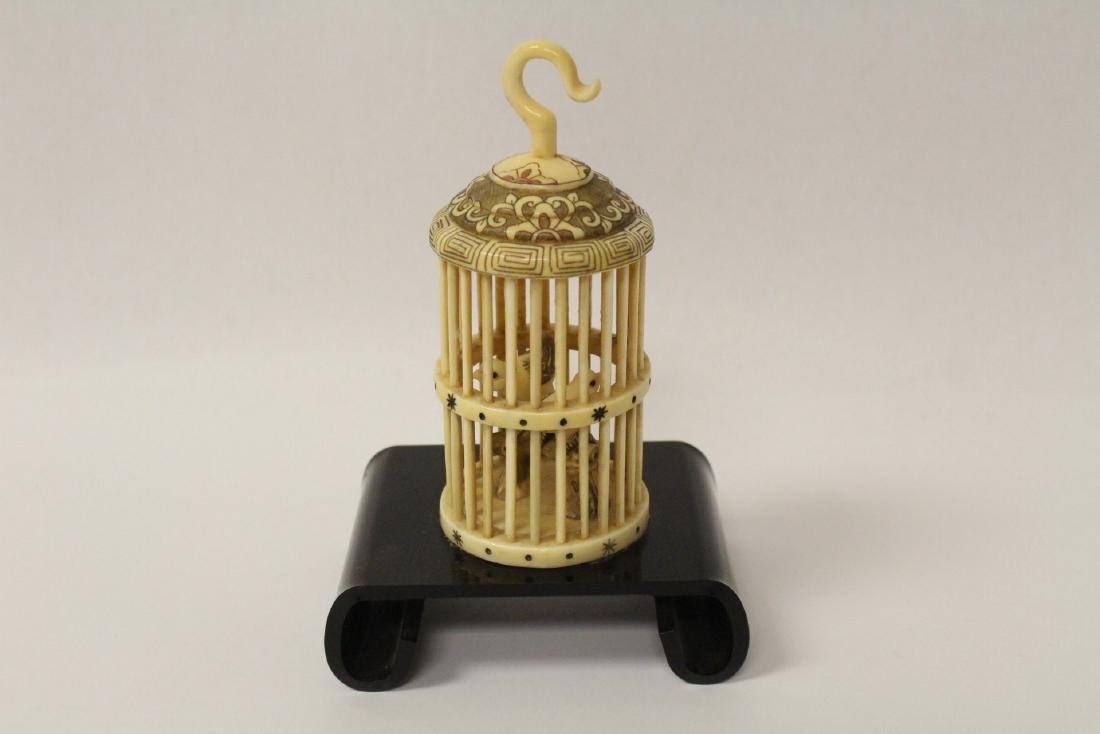 A bone carved bird cage with bird