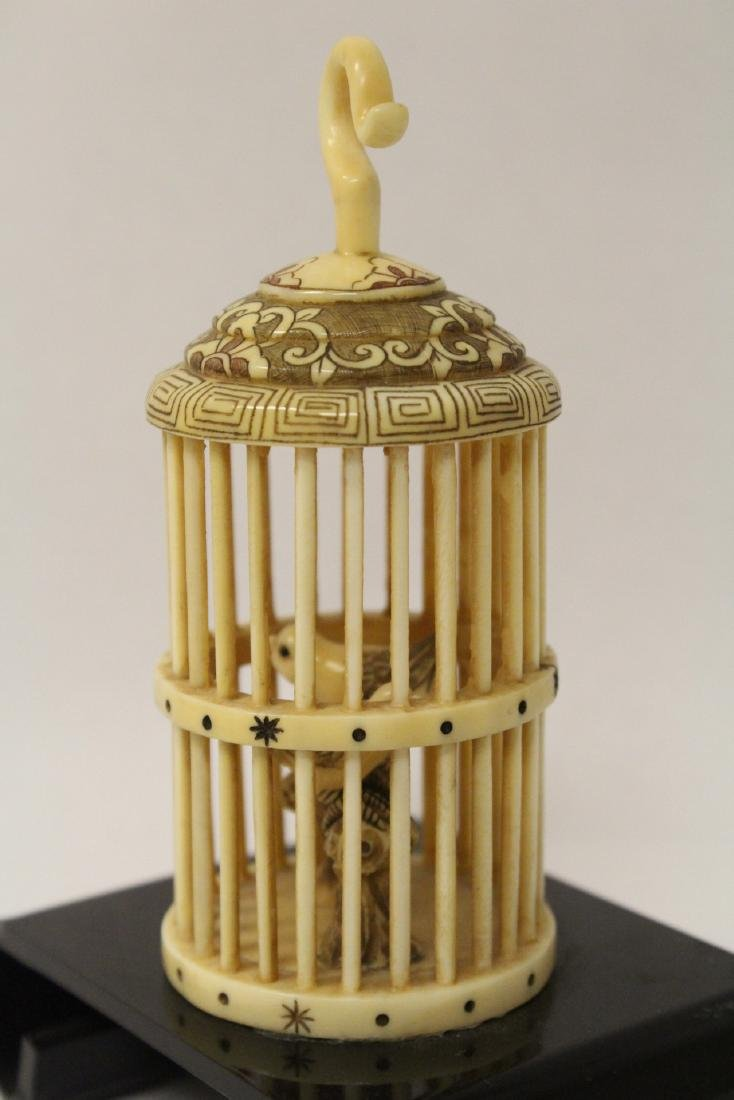 A bone carved bird cage with bird - 4