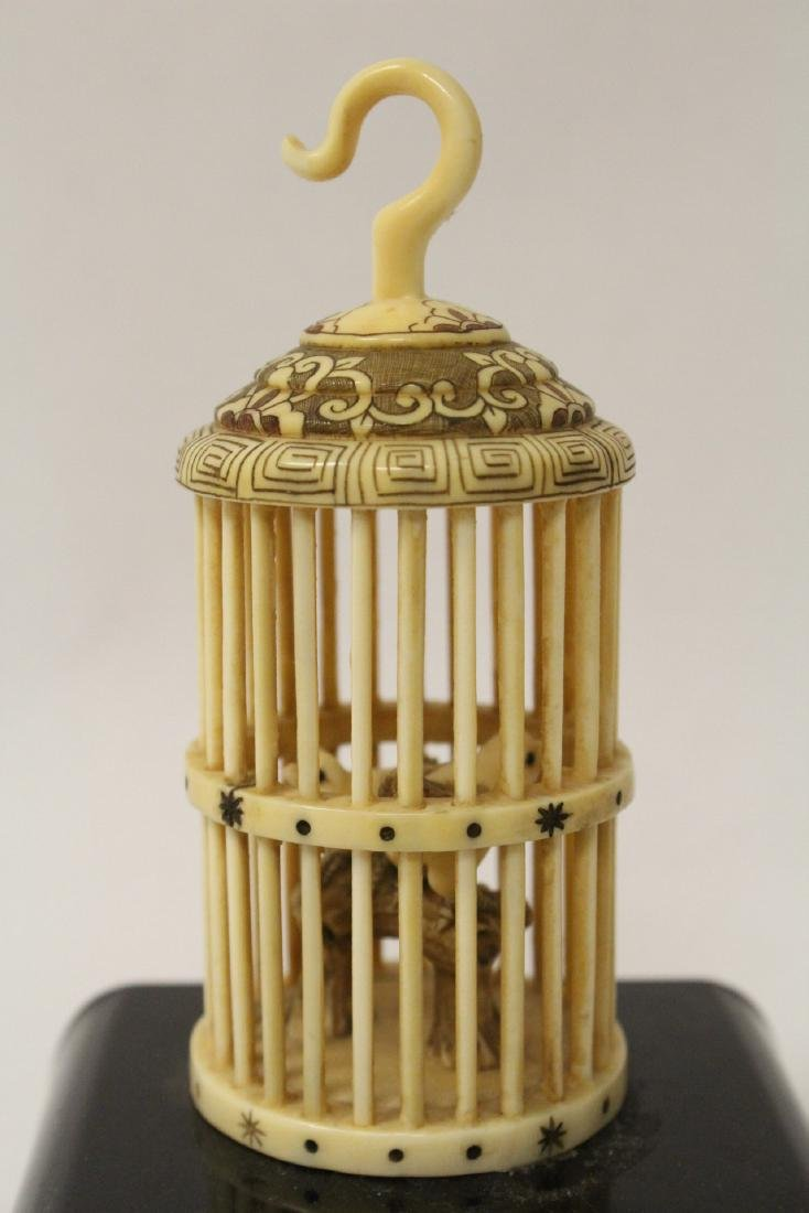 A bone carved bird cage with bird - 6